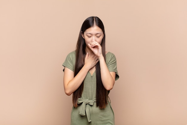 Asian young woman feeling ill with a sore throat and flu symptoms, coughing with mouth covered