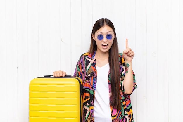 Азиатская молодая женщина чувствует себя счастливым и взволнованным гением после реализации идеи, весело поднимая палец, эврика !. концепция праздников