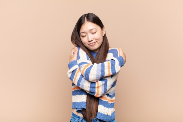 Asian young woman feeling in love, smiling, cuddling and hugging self, staying single, being selfish and egocentric