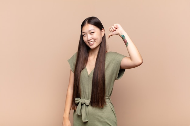 Asian young woman feeling proud, arrogant and confident isolated