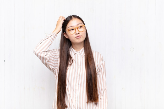 Asian young woman feeling puzzled and confused, scratching head and looking to the side