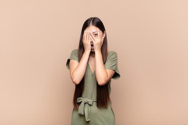 怖いまたは恥ずかしいと感じているアジアの若い女性