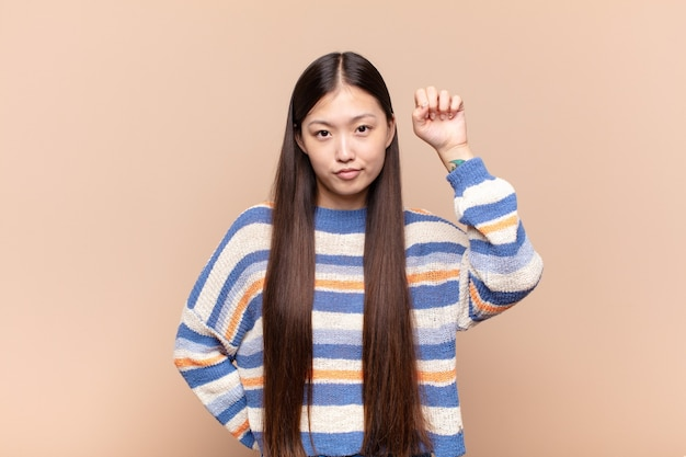 Asian young woman feeling serious, strong and rebellious isolated