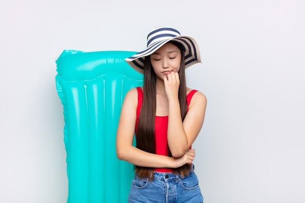 Asian young woman feeling serious, thoughtful and concerned, staring sideways with hand pressed against chin. summer concept
