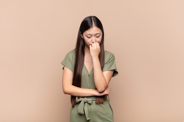 Asian young woman feeling serious, thoughtful and concerned, staring sideways with hand pressed against chin