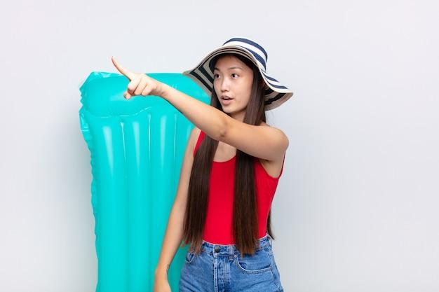 아시아 젊은 여성은 충격과 놀라움을 느끼고 놀랍고 입을 벌린 표정으로 경외심을 느끼며 위쪽을 바라보고 있습니다. 여름 개념