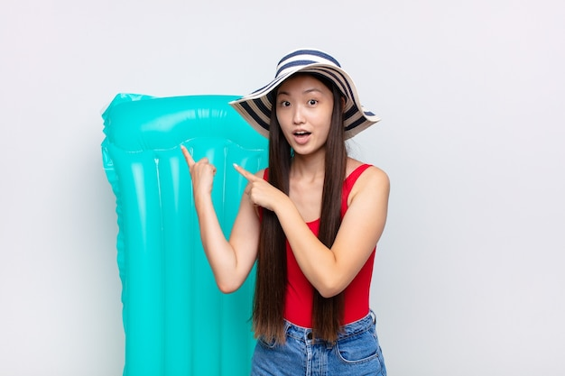 驚いた、口を開けた表情で側面のコピースペースを指して、ショックを受けて驚いたアジアの若い女性。夏のコンセプト