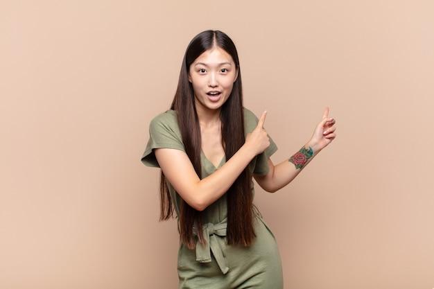 驚いた、口を開けた表情で側面のコピースペースを指して、ショックを受けて驚いたアジアの若い女性