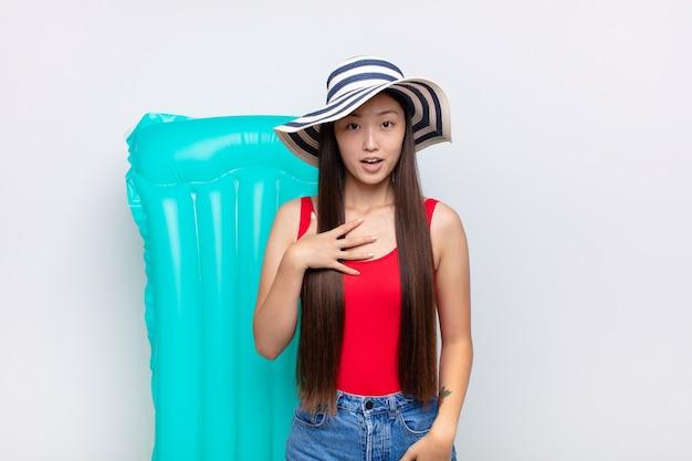 アジアの若い女性は、胸に手を当てて口を開けて、ショックを受け、驚き、驚きを感じ、誰だ、私?