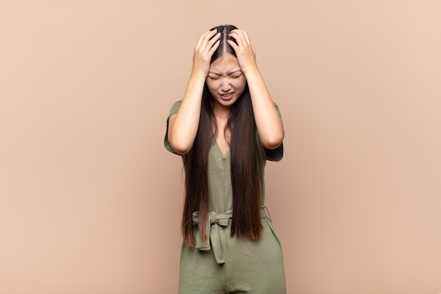 Asian young woman feeling stressed and frustrated, raising hands to head