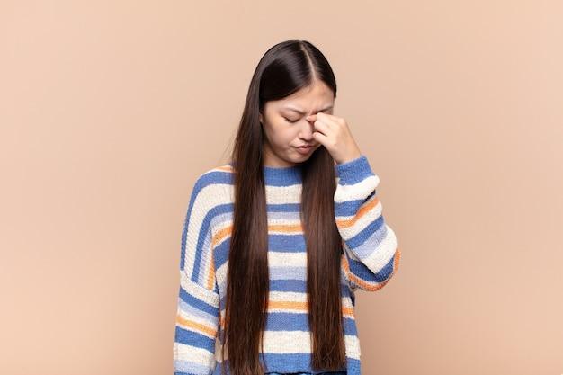 Азиатская молодая женщина чувствует себя подчеркнутой, несчастной и разочарованной изолированной