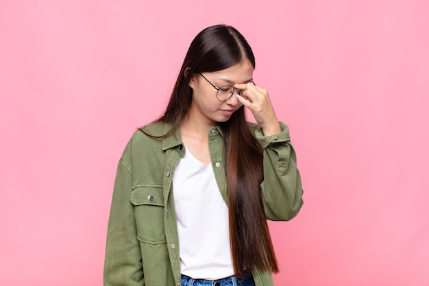 Asian young woman feeling stressed, unhappy and frustrated, touching forehead and suffering migraine of severe headache