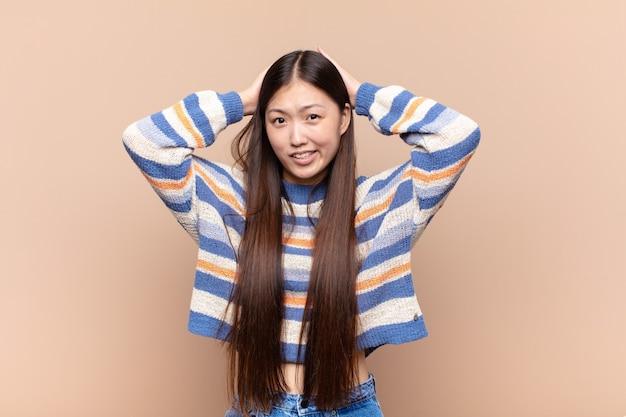 ストレス、心配、不安、または恐怖を感じ、頭に手を置いて、誤ってパニックに陥るアジアの若い女性