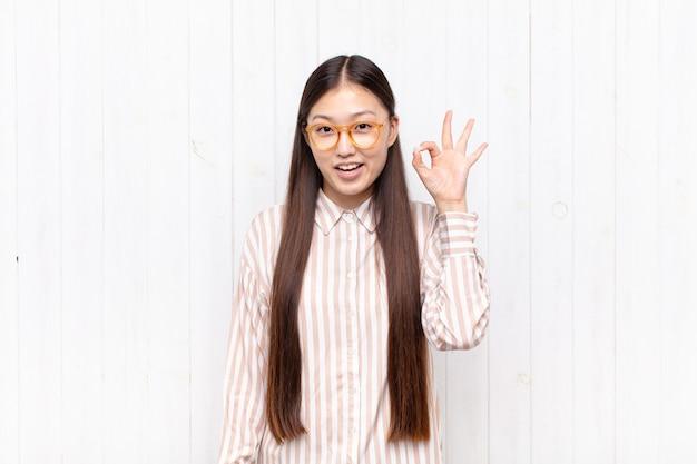 성공과 만족을 느끼는 아시아 젊은 여자, 입 벌리고 웃고, 손으로 괜찮아 기호 만들기