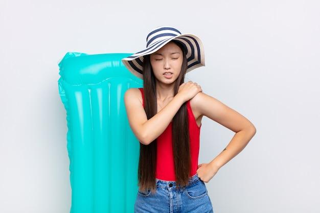 Молодая азиатская женщина чувствует усталость, стресс, тревогу, разочарование и депрессию, страдает от боли в спине или шее. летняя концепция
