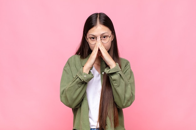 Азиатская молодая женщина чувствует беспокойство, надежду и религиозность, верно молится, прижав ладони, умоляя о прощении