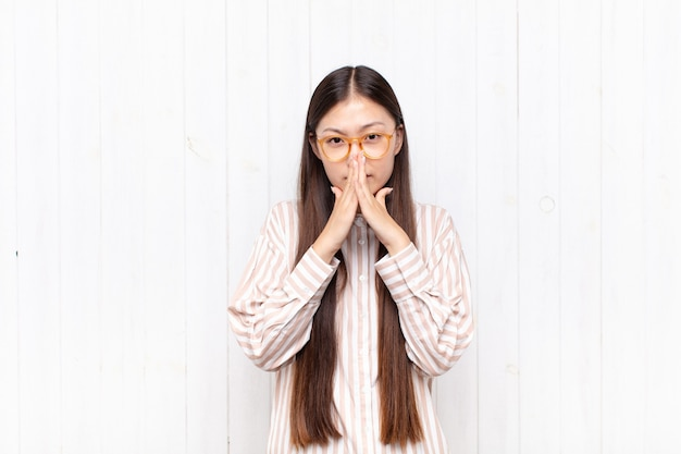 Asian young woman feeling worried, hopeful and religious