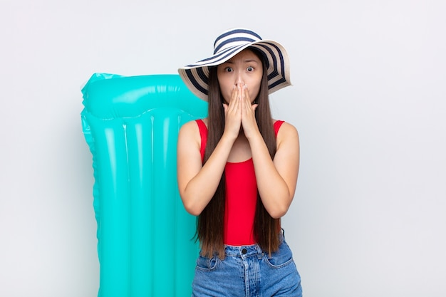 Asian young woman feeling worried, upset and scared, covering mouth with hands, looking anxious and having messed up. summer concept