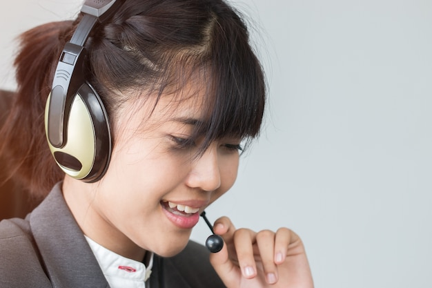 アジア人の若い女性フレンドリーなオペレーターまたはコールセンターのエージェントとヘッドセット
