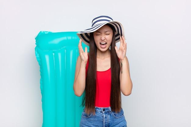 アジアの若い女性は猛烈に叫び、ストレスを感じ、空中で手を上げてイライラし、なぜ私なのかを言いました。夏のコンセプト