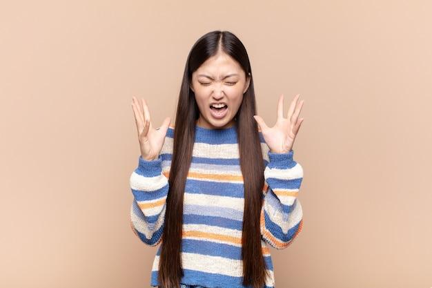 アジアの若い女性が猛烈に叫び、ストレスを感じ、空中に手を上げてイライラし、なぜ私が