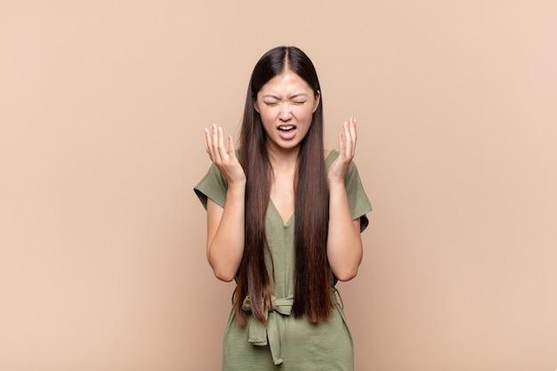 Азиатская молодая женщина яростно кричит, чувствуя стресс и раздражение, подняв руки вверх, говоря, почему я