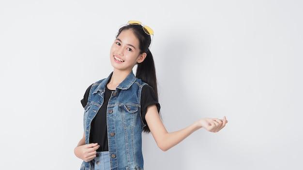 白い背景でポーズをとるアジアの若い女性のジェスチャー。陽気で自信を持って表現します。ミニハートなどのジェスチャーを表示する大丈夫親指を立てるか、指摘します。幸せな驚きの興奮と驚きのジャケットジーンズ。