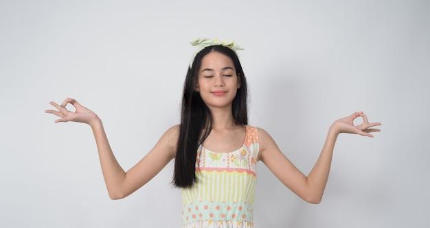 白い背景でポーズをとるアジアの若い女性のジェスチャーは、陽気で自信を持って見せることを表します