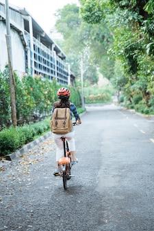 アジアの若い女性は彼女の折りたたみ自転車に乗ってヘルメットとバッグを着て行く