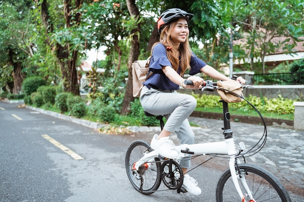 Asian young woman goes wearing a helmet and a bag riding her folding bicycle