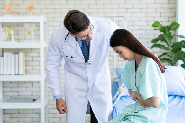 Asian young woman got a painful stomachache during resting in the hospital. caucasian specialist doctor come to meet serious woman patient and talking about her illness crisis. healthcare concept.