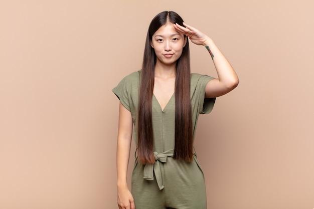 Азиатская молодая женщина приветствует военным салютом в знак чести и патриотизма, проявляя уважение