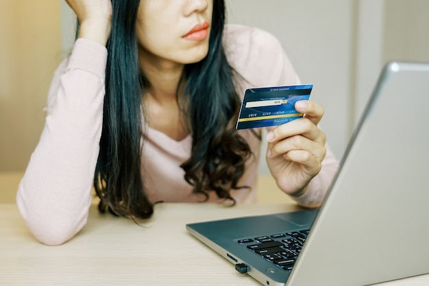 Asian young woman hands holding credit card and using laptop smartphone