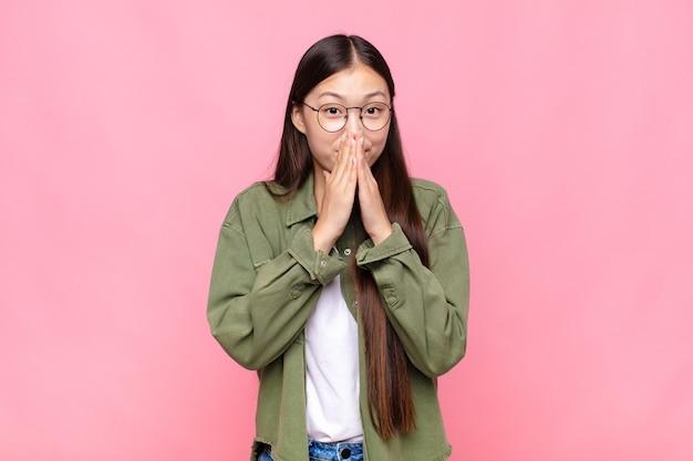 아시아 젊은 여자가 행복하고 흥분, 놀라고 놀란 손으로 입을 덮고, 귀여운 표정으로 킥킥 웃고