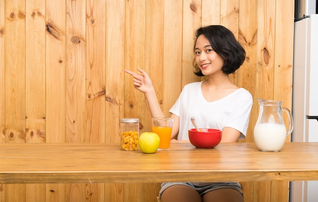 Asian young woman having breakfast milk pointing finger to the side
