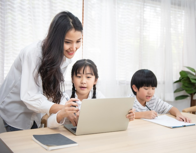 Asian young woman help her son do homework with daughter using laptop sit beside on table in living room at home.
