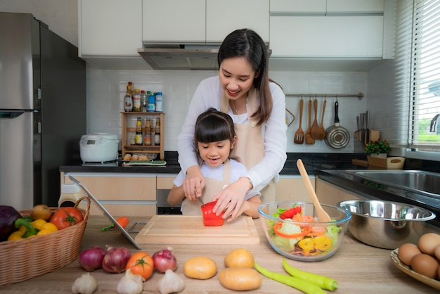 Asian young woman and her daughter cooking salad for lunch
