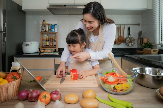 Asian young woman and her daughter cooking salad for lunch.