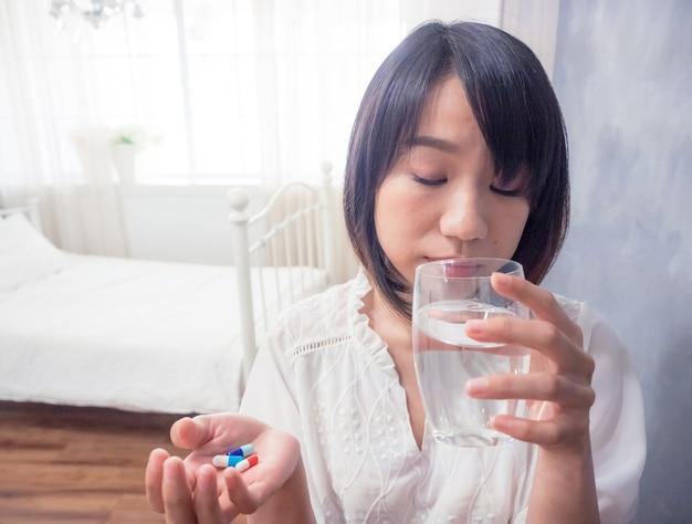 물과 약 한 잔을 들고 아시아 젊은 여자.