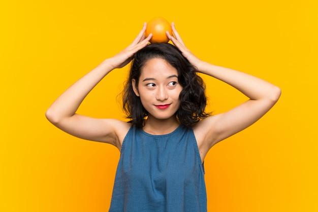 Азиатская молодая женщина держит апельсин