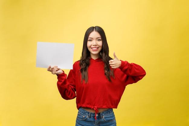白紙のボードや紙を保持しているアジアの若い女性。