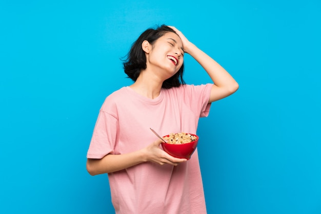 Asian young woman holding a bowl of cereals has realized something and intending the solution