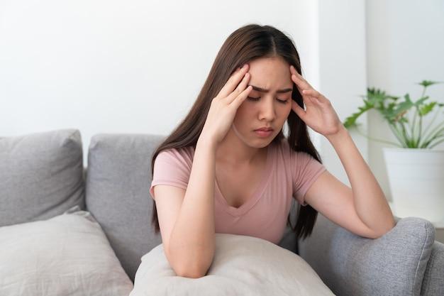 彼女の頭を保持しているアジアの若い女性、彼女は自宅のリビングルームのソファーソファに座っている頭痛を持っています。