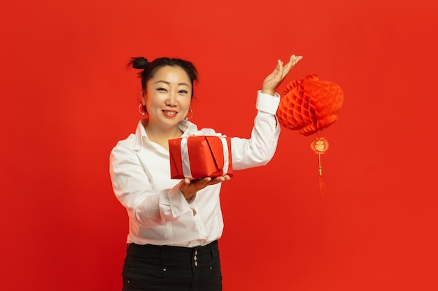 Asian young woman holding lantern and gift on red wall