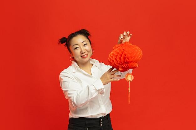 赤い壁に提灯を保持しているアジアの若い女性