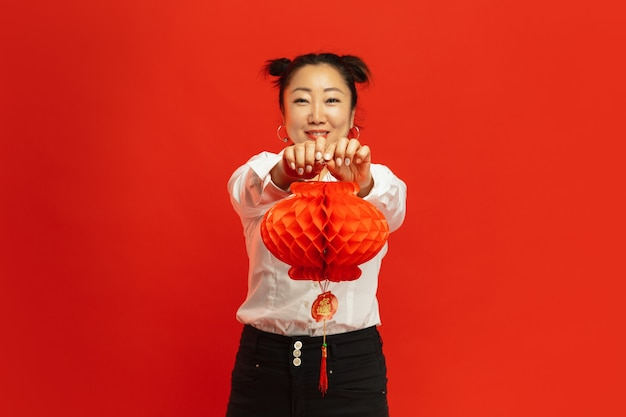 Asian young woman holding lantern on red wall