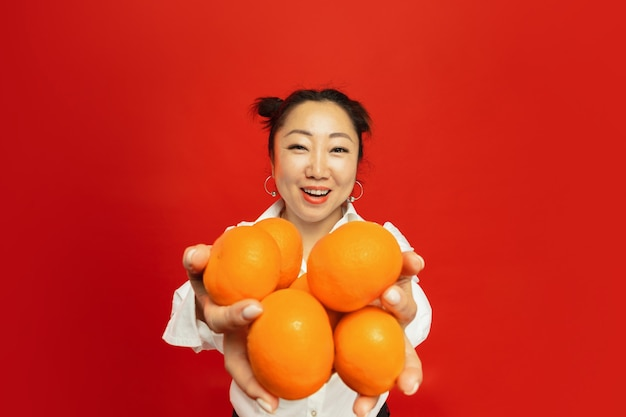 赤い壁にみかんを保持しているアジアの若い女性