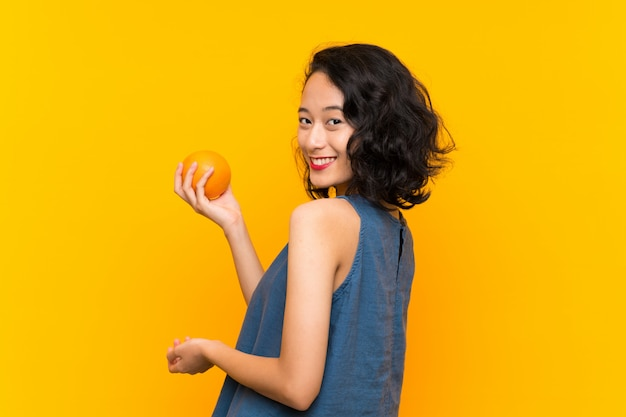 Asian young woman holding an orange