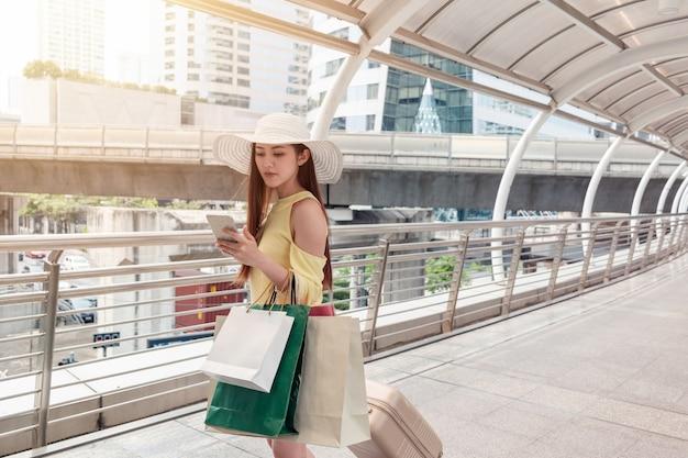 スマートフォンを使って紙袋を持ち、都会の廊下で荷物を引っ張るアジアの若い女性