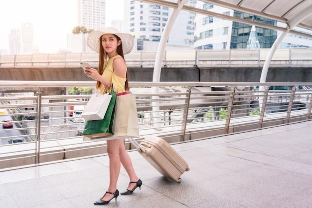 スマートフォンを使って買い物をする紙袋を持ち、廊下で荷物を引っ張るアジアの若い女性